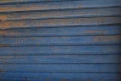 Gammal blå dörr för metallbakgrundsstål och smutsig slutare för abstrakt textur Arkivbild