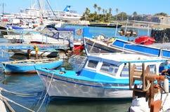 Gammal blå fiskebåt i en havsport Arkivbild