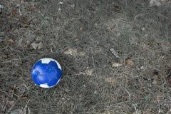 Gammal blå fotbollboll på gräs arkivfoto