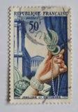 Gammal blå fransk portostämpel för N med en bild av en kvinnlig hand som rymmer stilfulla smycken royaltyfria bilder