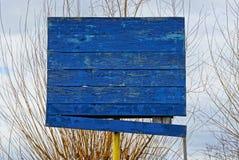 Gammal blå träbasketmålbräda mot bakgrunden av filialer och himmel royaltyfri fotografi