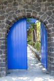Gammal blå träträdgårds- dörr på stenväggen fotografering för bildbyråer