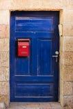 Gammal blå woodlsmutsdörr med den röda brevlådan och rostiga metalllockas en härlig tappningbakgrund Arkivfoton