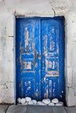 Gammal blå dörr för Grunge i den Oia staden, Santorini, Grekland Royaltyfria Foton