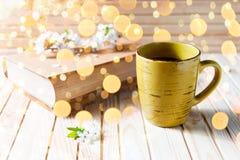 Gammal bok, kopp kaffe bredvid vita blommor för vår på trätextur med doldbokeh Royaltyfria Foton