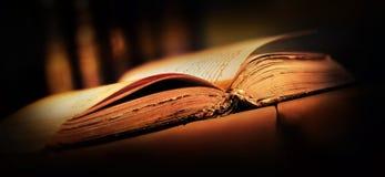 Gammal bok med den öppna sidor och strålen av ljus arkivfoton