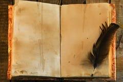 Gammal bok med sjaskiga sidor och den svarta vingpennan, bästa sikt Arkivbilder