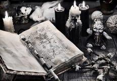 Gammal bok med svarta magiska pass, den läskiga dockan, svartstearinljus och pentagram Arkivfoton