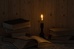 Gammal bok och ett stearinljus Arkivbilder
