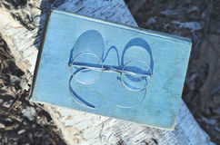 Gammal bok och tappninganblickar eller glasögon utomhus Royaltyfri Bild