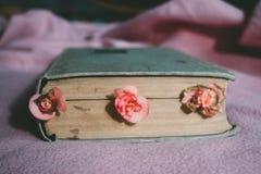 Gammal bok och torkade blommor arkivfoto
