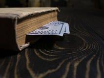 Gammal bok och tvåhundra dollar bokmärke i en tjock bok bok på bakgrunden av en trätabell arkivbilder