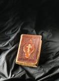 Gammal bok på svart bakgrund Forntida kristen bibel Antikvitet s Royaltyfria Foton