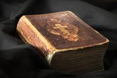 Gammal bok på svart bakgrund Forntida kristen bibel AntikvitetH Fotografering för Bildbyråer