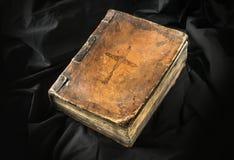 Gammal bok på svart bakgrund Forntida kristen bibel AntikvitetH Royaltyfria Foton