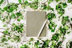 Gammal bok, penna och filialer med sidor och blommor på vit bakgrund Royaltyfria Bilder