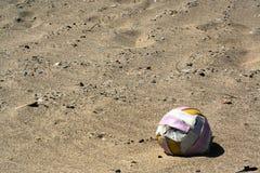 Gammal boll på sanden Arkivbild