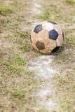 Gammal bollfotboll på gräs Arkivbild