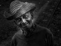 Gammal bonde med sugrörhatten royaltyfria bilder