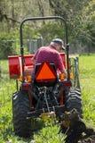 Gammal bonde Plowing His Garden med en enkel nedersta plog Arkivbild