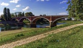 Gammal bro över den Kupa floden i Sisak, Kroatien royaltyfri fotografi