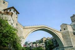 Gammal bro av Mostar under en solig eftermiddag, med den gamla staden som är synlig i bakgrunden arkivfoto