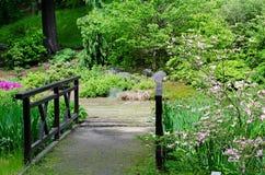 Gammal bro i romantikerträdgård Arkivfoto