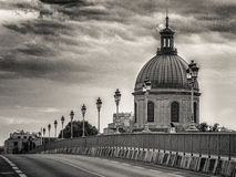 Gammal bro och kyrklig och molnig himmel i Toulouse Frankrike Arkivbild