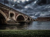 Gammal bro och molnig himmel i Toulouse Frankrike Arkivbild