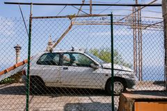 Gammal bruten bil bak staketet mot den blåa himlen royaltyfria foton