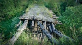 Gammal bruten träbro över floden, bakgrund för grönt gräs arkivfoto