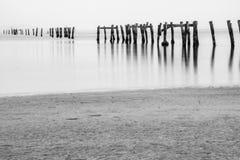 Gammal brygga på stranden på grå färger om dagen Royaltyfria Bilder