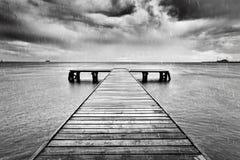 Gammal brygga, pir på havet Svartvitt regn Fotografering för Bildbyråer