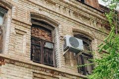 Gammal byggande vägg med luft som betingar och med lagt och stigit ombord upp fönster royaltyfri fotografi