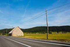 Gammal byggnad från stenen och elkraftkolonn nära huvudvägen i berg i bygd i Kroatien Royaltyfria Foton