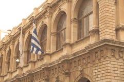 Gammal byggnad med den grekiska flaggan fotografering för bildbyråer
