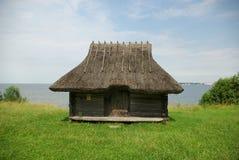 Gammal byggnad med grästaket vid havet arkivbild