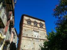 Gammal byggnad med steg ombord övre fönster mot den blåa himlen i ramen av andra hus och träd, Maratea, Italien arkivbilder