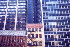 Gammal byggnad mellan moderna skyskrapor i New York City Royaltyfri Foto