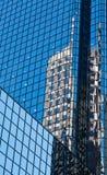 Gammal byggnad reflekterad i modernt blått Glass torn Royaltyfri Fotografi