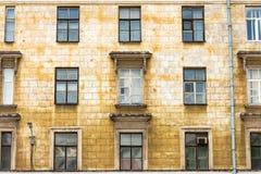 Gammal byggnad som kräver reparation i fönster och balkonger för dåligt villkor fotografering för bildbyråer