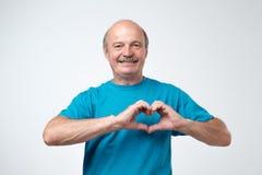Gammal caucasian man i blå t-skjorta danande ut ur handhjärta arkivfoton