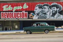 Gammal Claaic bilkörning förbi propagandatecknet Fotografering för Bildbyråer