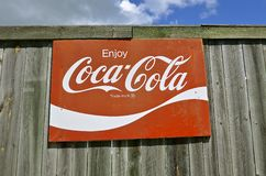Gammal coca - colatecken på ett trästaket Fotografering för Bildbyråer