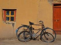 Gammal cykel för svart tappning med stora hjul på väggen av det gula byhuset Arkivbilder