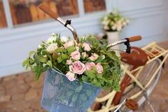 Gammal cykel med en korg av rosor mot väggen i pastellfärgade färger Dekorativ cykelst?llning f?r v?xter och blommor H?rligt r royaltyfri bild