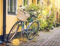 Gammal cykel med en korg på en gammal gatabakgrund royaltyfri bild