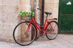 Gammal cykel med korgen som täckas med blommor som lutar på stenwa Arkivfoto