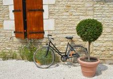 Gammal cykel mot väggen Arkivbild