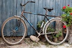 Gammal cykel nära ett blått trästaket i by royaltyfri bild